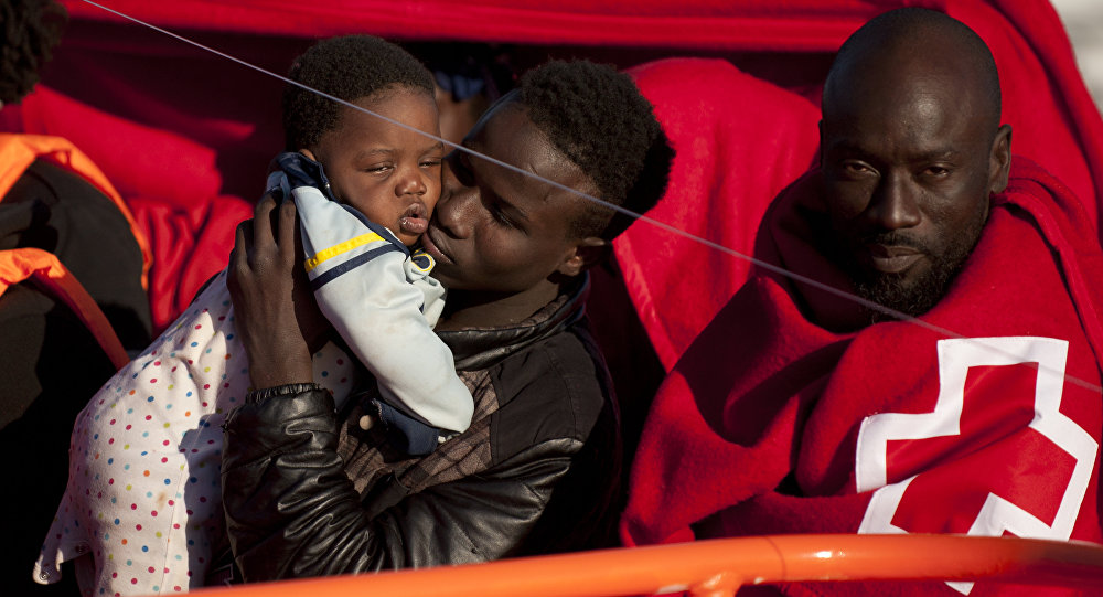 A migrants wrapped in a red cross blanket holds a child on arrival into the southern Spanish port of Malaga on January 27, 2016 after an inflatable boat carrying 55 Africans, seven of them women and six chidren, was rescued by the Spanish coast guard off the Spanish coast (File)