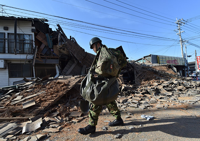 A member of the self defense forces walks past a collapsed house in Mashiki, Kumamoto prefecture on April 16, 2016