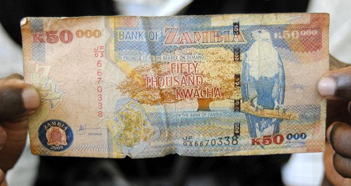 A man displays a 50,000 Kwacha note in Lusaka, Zambia, January 23, 2012