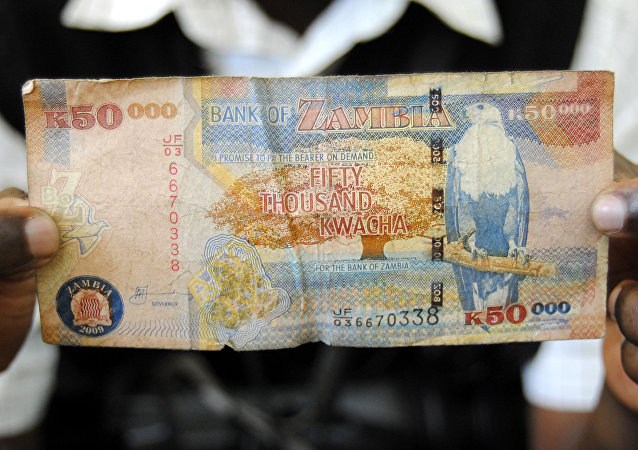 A man displays a 50,000 Kwacha note in Lusaka, Zambia, January 23, 2012