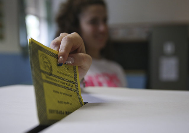 A woman casts her ballot for a referendum on the duration of offshore drilling concessions, in Pavia, Italy, Sunday, April 17, 2016