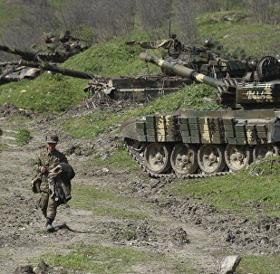 A soldier of the defense army of Nagorno-Karabakh walks past tanks at a field position outside the village of Mataghis, some 70km north of Karabakh's capital Stepanakert, on April 6, 2016