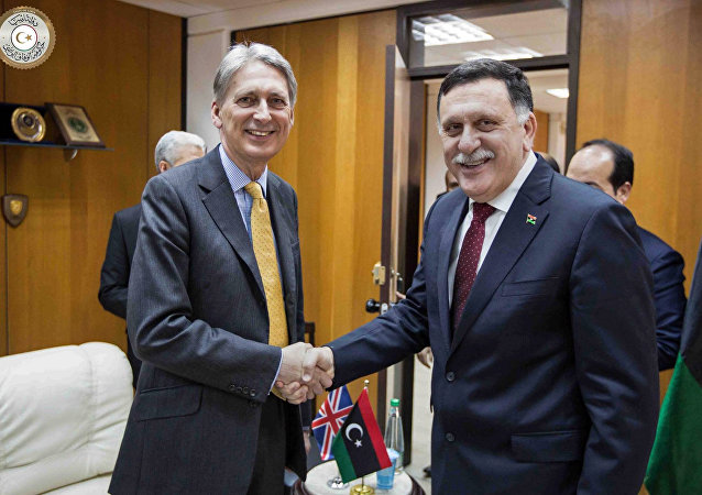 In this photo provided by the Libyan Government of National Accord, Libyan prime minister-designate Fayez Serraj , right and British Foreign Secretary Philip Hammond shake hands for photographers in Tripoli, Libya, Monday, April 18, 2016.
