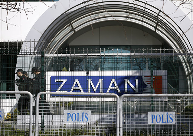 Riot police officers walk by the headquarters of Zaman newspaper in Istanbul