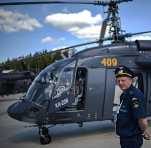 A pilot stands next to a Ka-226 helicopter at the ARMY-2015 international military technical forum held outside Moscow.