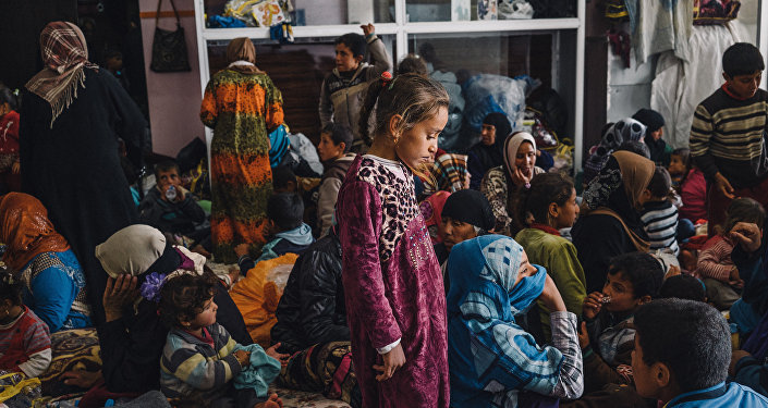 Child stands among women and children in a building housing displaced civilians, in Makhmour, east of Mosul, Iraq (File)