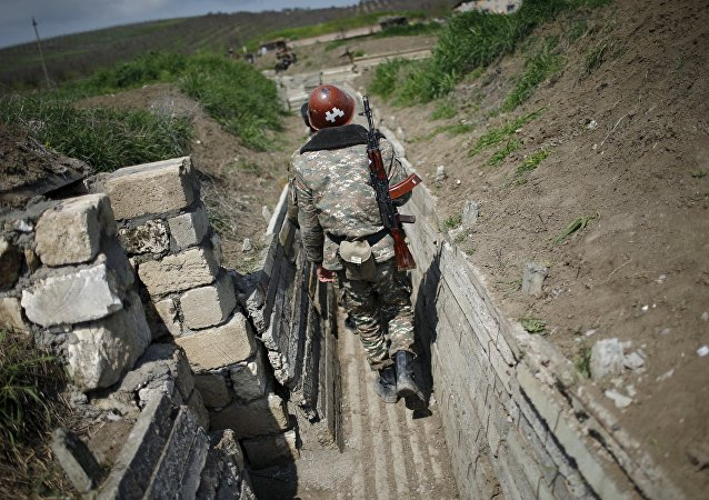 Ethnic Armenian soldiers walk in a trench at their position near Nagorno-Karabakh's town of Martuni, April 8, 2016