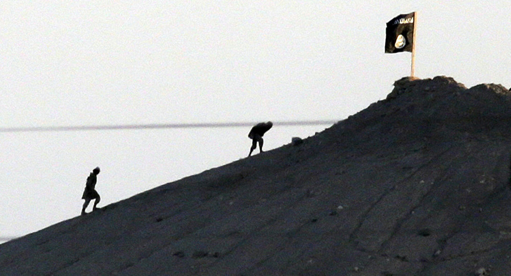 Shot with an extreme telephoto lens and through haze from the outskirts of Suruc at the Turkey-Syria border, militants with the Islamic State group are seen after placing their group's flag on a hilltop at the eastern side of the town of Kobani, Syria (File)