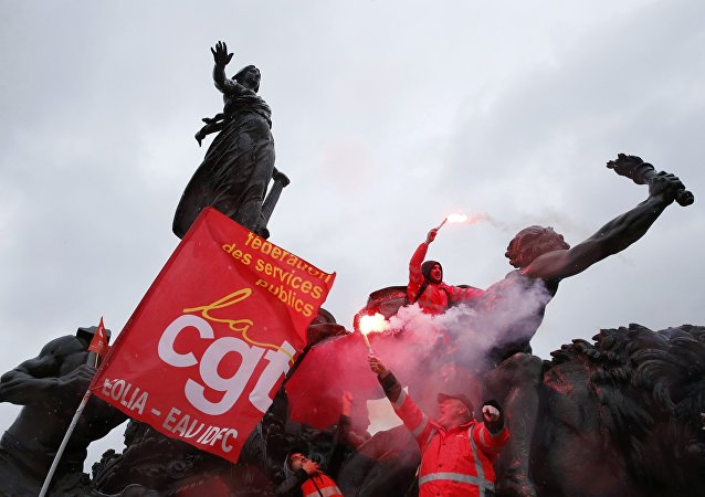 French CGT labour union workers hold safety flares as they stand on the statue of the Place de la Nation during a demonstration against the French labour law proposal in Paris.