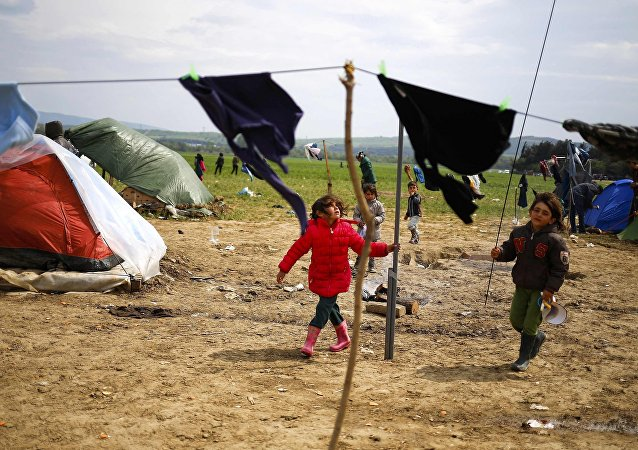 Children play during heavy winds at a makeshift camp for migrants and refugees at the Greek-Macedonian border near the village of Idomeni, Greece, April 11, 2016.