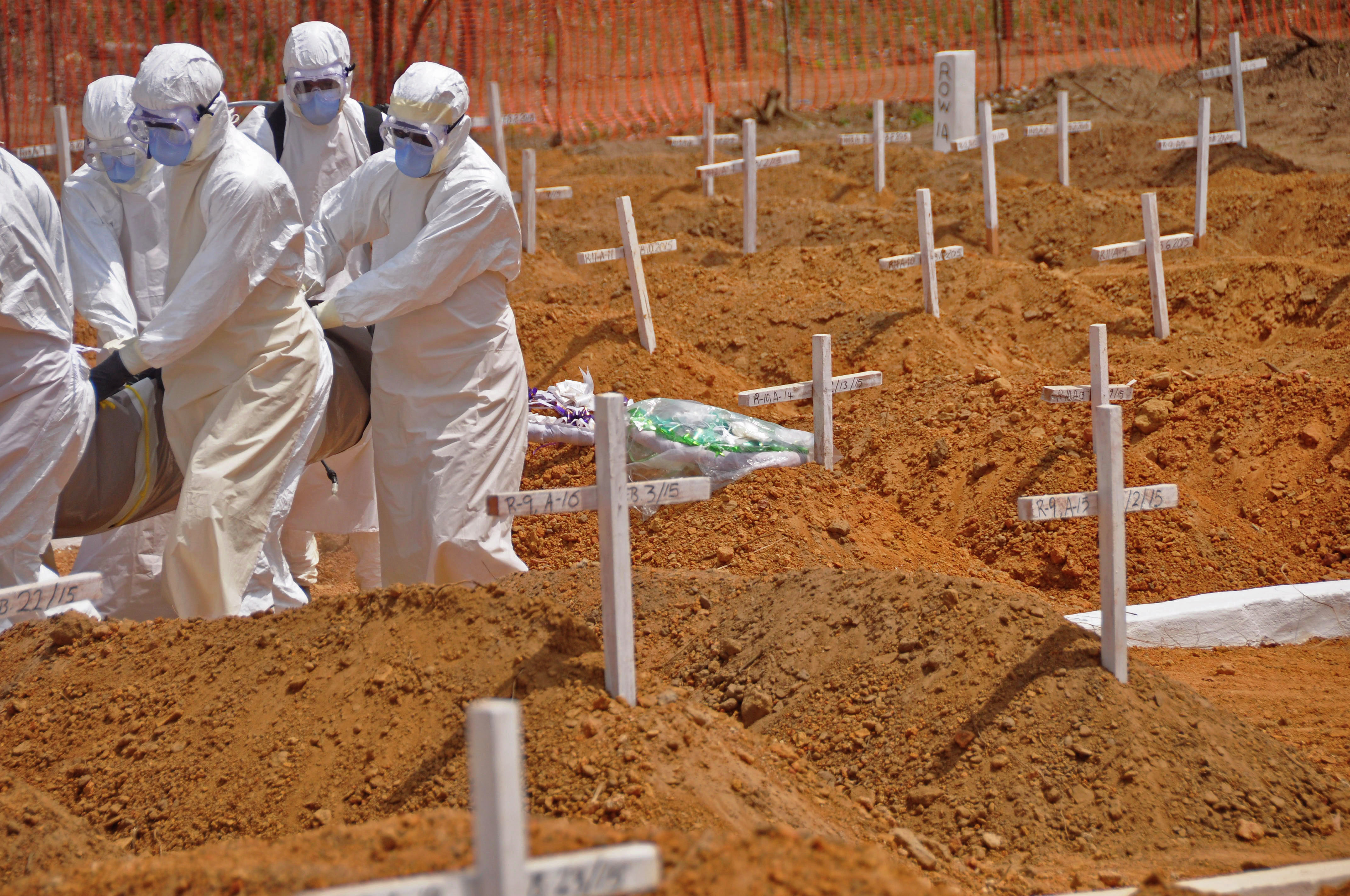 Health workers carry the body, of a person that they suspected died from the Ebola virus at a new graveyard on the outskirts of Monrovia, Liberia, Wednesday, March 11, 2015