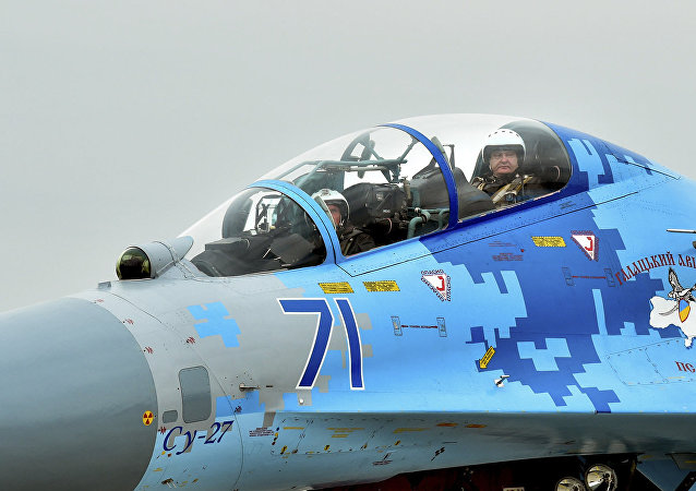 Ukrainian President Petro Poroshenko right, sits inside a Su-27 fighter before his flight in Zaporizhzhya, Ukraine Wednesday,Oct. 14, 2015