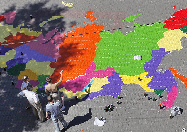 Graffiti artists paint a map of Russia in front of the building of Moscow State Mapping and Geodesy University