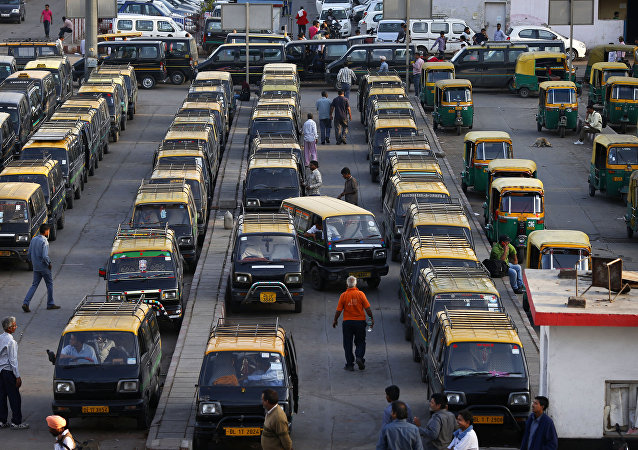 In this Monday, March 24, 2014 photo, traditional black-and-yellow licensed cabs stand parked waiting for customers at a railway station in New Delhi, India