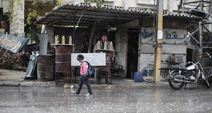 A Syrian schoolboy walks under the rain in Kafr Batna, in the Eastern Ghouta area, on the outskirts of the capital Damascus (File)