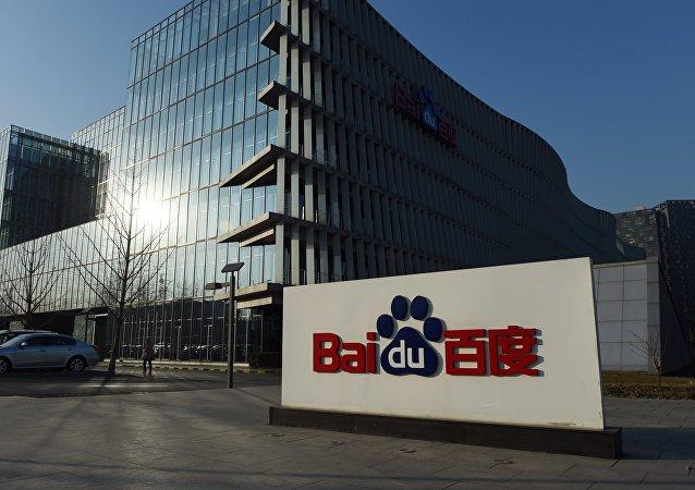 A photographer walks past the logo of Baidu Inc.