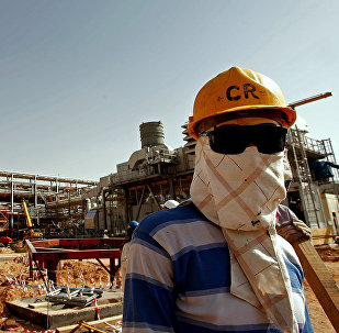 An Asian worker covers his face to protect it from the dust and the blazing sun at the site of Saudi Aramco's (the national oil company) Al-Khurais central oil processing facility under construction in the Saudi Arabian desert, 160 kms east of the capital Riyadh (File)