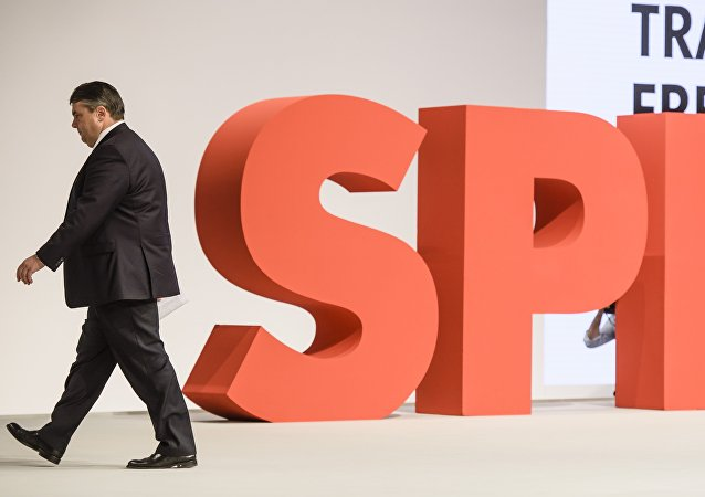 German Social Democratic Party ( SPD ) leader, German Vice Chancellor, Economy and Energy Minister Sigmar Gabriel walks by a giant logo of his party at the SPD annual federal congress in Berlin on December 12, 2015.