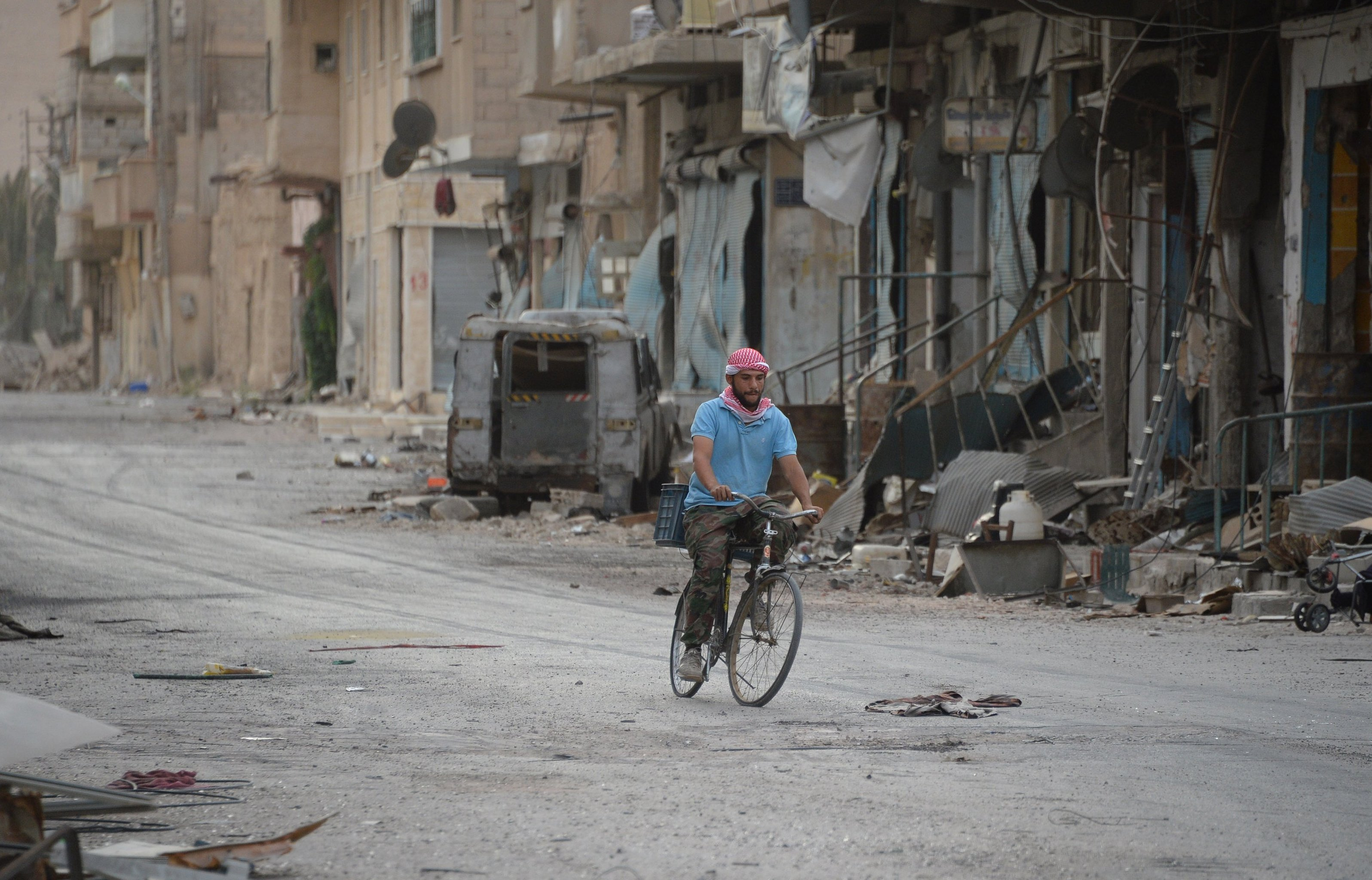 A man rides a bicycle in Palmyra.