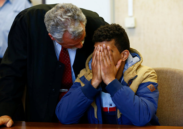 Lawyer Ruediger Buhr (L) speaks to his client, a 23-year-old Algerian who faces charges of assaults on woman during New Year's Eve celebrations in Cologne, at a regional court in Cologne, western Germany, May 6, 2016.