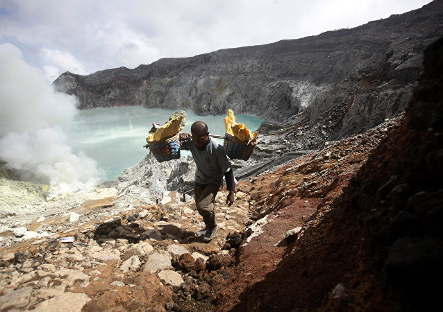 In this April 16, 2016 photo, Marzuki, a sulfur miner, carries baskets of sulfur as he climbs up from the crater of Mount Ijen in Banyuwangi, East Java, Indonesia