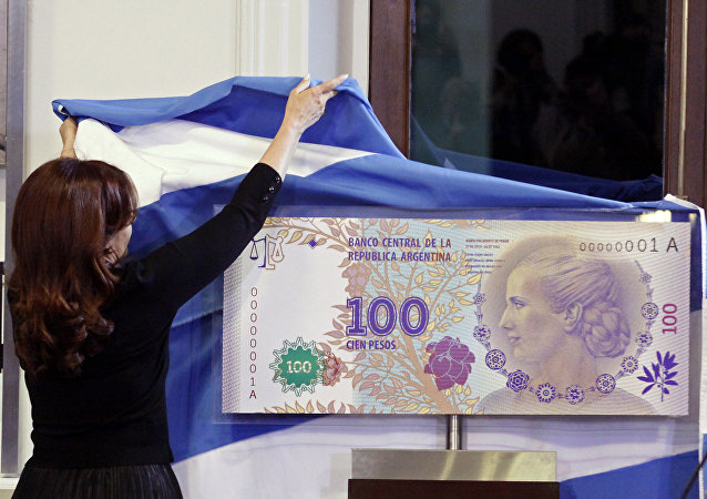 FILE - In this July 25, 2012 photo, Argentina's President Cristina Fernandez unveils an archetype of the new 100 Argentine pesos bill bearing the profile of former late first lady Maria Eva Duarte de Peron, better known as Evita, at the government palace in Buenos Aires, Argentina