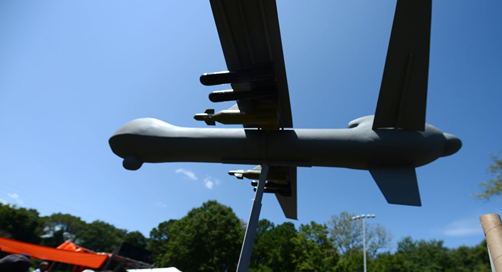 Protesters against the use of drone strikes by the US military hold a model of a drone aircraft during the March On Wall Street South rally in Charlotte, North Carolina on September 2, 2012.