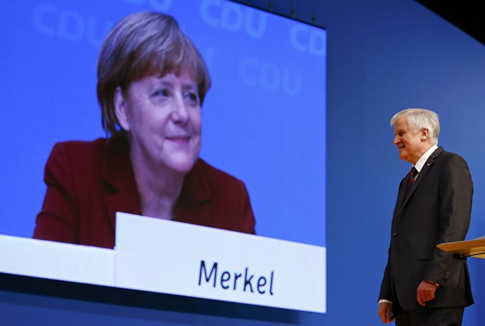 German Chancellor and leader of the Christian Democratic Union (CDU) Angela Merkel is seen on a video screen as Bavarian Prime Minister and head of the Christian Social Union (CSU) Horst Seehofer makes a speech at the CDU party congress in Karlsruhe, Germany in this December 15, 2015.