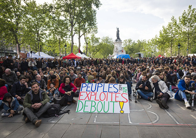 A protester holds a placard reading 'Exploited people stand up!' as people gather for the general assembly of the Nuit Debout movement in Paris on May 15, 2016