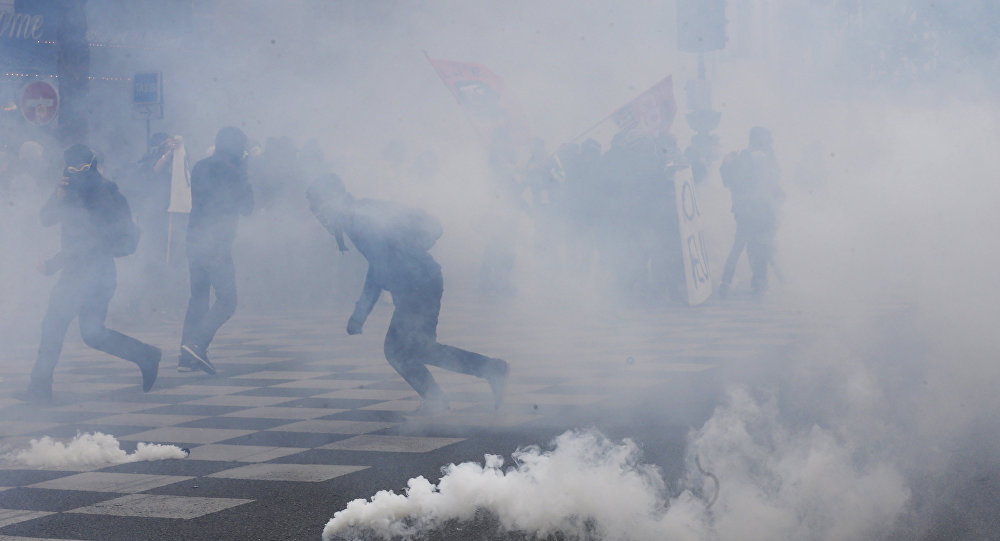 Protesters run from tear gas canisters during clashes with police at a demonstration after the French government used the constitution's Article 49,3 to bypass parliament and force through a controversial labour reform bill, on May 17, 2016, in Paris