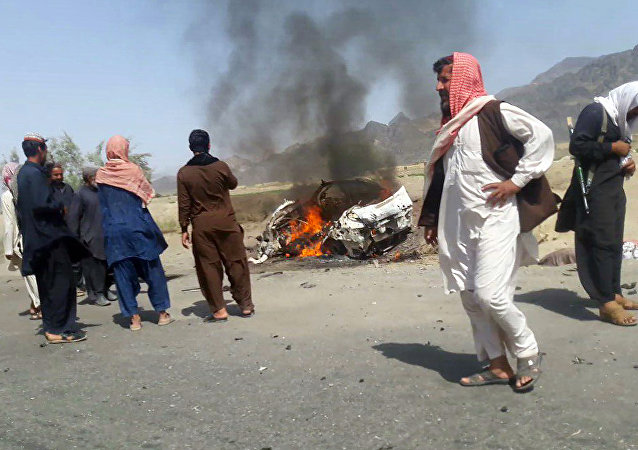 This photograph taken on May 21, 2016 shows Pakistani local residents gathering around a destroyed vehicle hit by a drone strike in which Afghan Taliban Chief Mullah Akhtar Mansour was believed to be travelling in the remote town of Ahmad Wal in Balochistan, around 160 kilometres west of Quetta.
