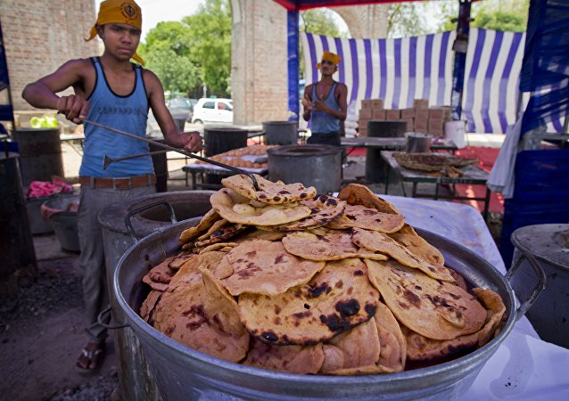 Workers prepare rotis, a type of Indian bread at the Bangla Sahib Sikh temple. File photo