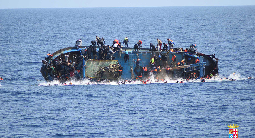 Migrants are seen on a capsizing boat before a rescue operation by Italian navy ships Bettica and Bergamini off the coast of Libya in this handout picture released by the Italian Marina Militare on May 25, 2016