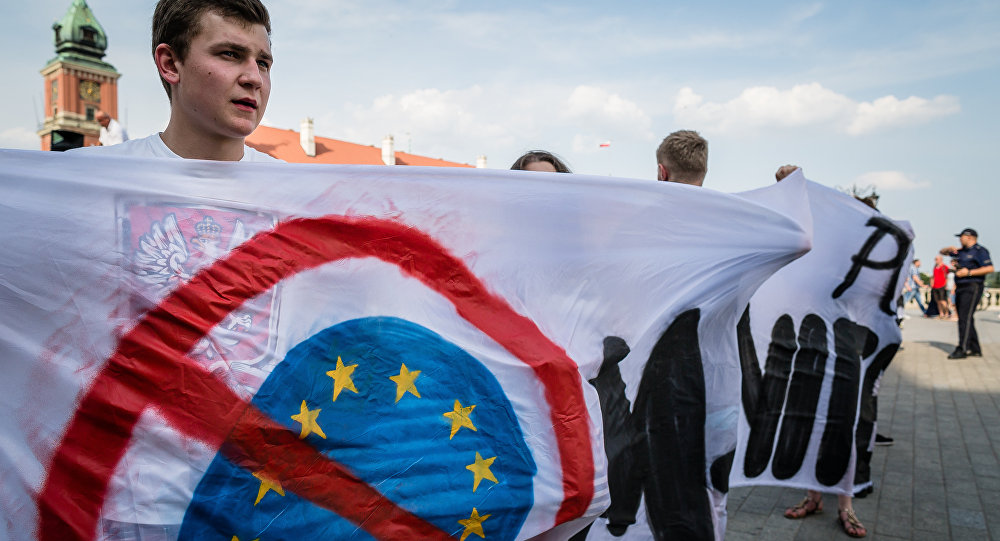 Polish farright activists hold anti-EU banner as they take part in demonstration against accepting over 2000 immigrants to Poland, Warsaw on a July 25, 2015