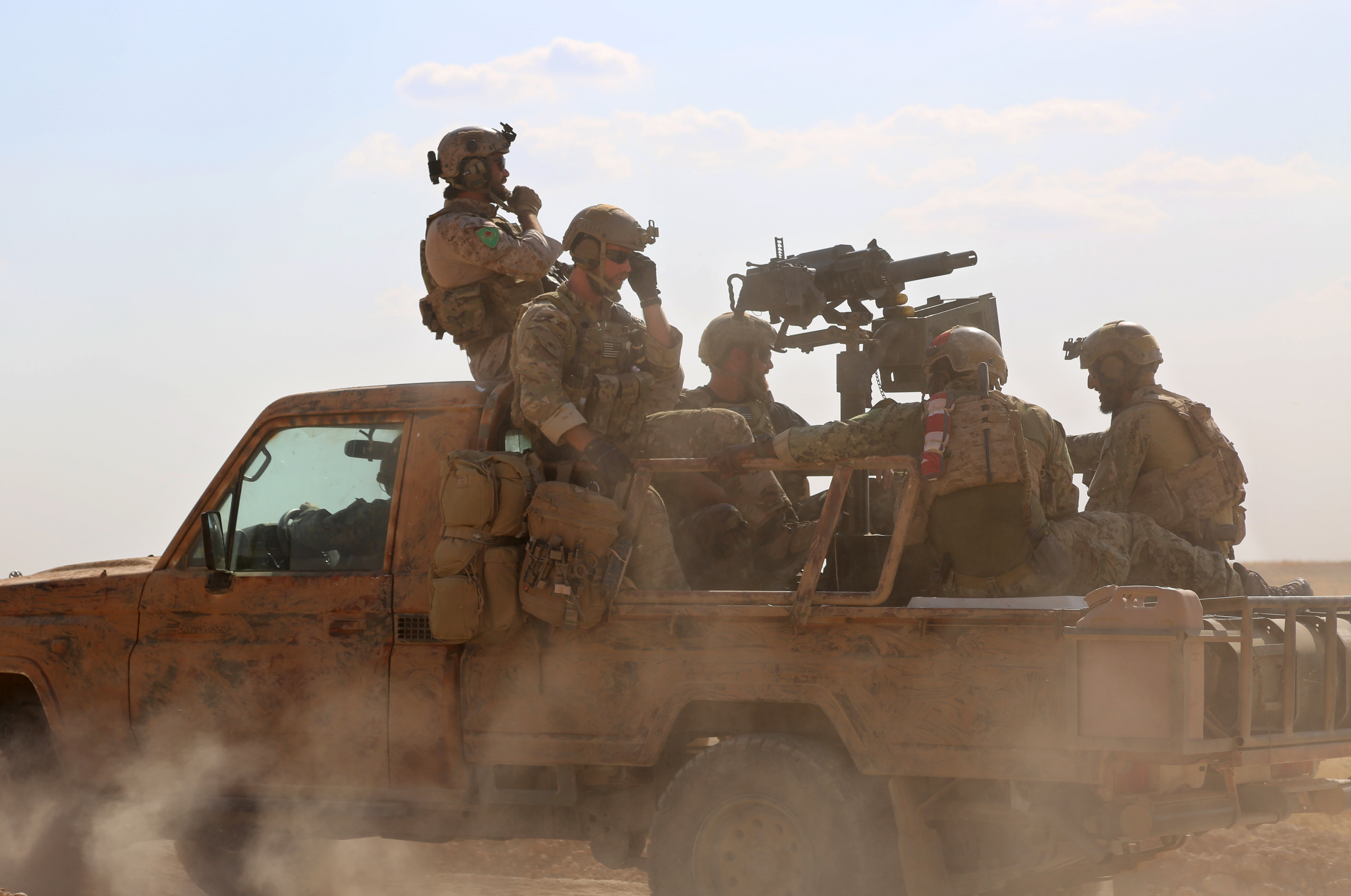 Armed men in uniform identified by Syrian Democratic forces as US special operations forces ride in the back of a pickup truck in the village of Fatisah in the northern Syrian province of Raqa on May 25, 2016