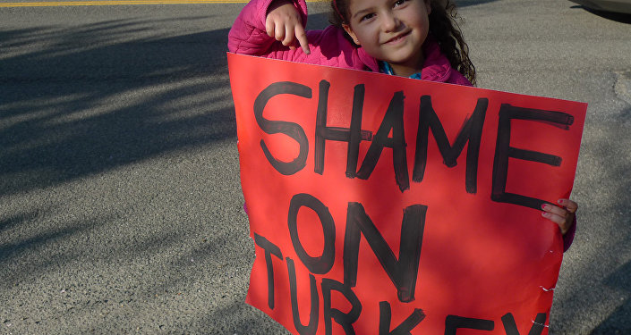 A child demonstrator holding the 'Shame on Turkey' sign.