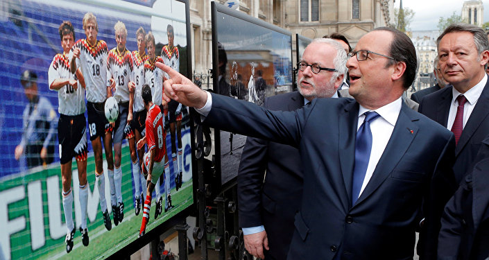 French President Francois Hollande (2ndL), flanked with French Soccer specialist Pierre Louis Basse (L), comment on a photo of Bulgarian soccer player Hristo Stoitchkov.
