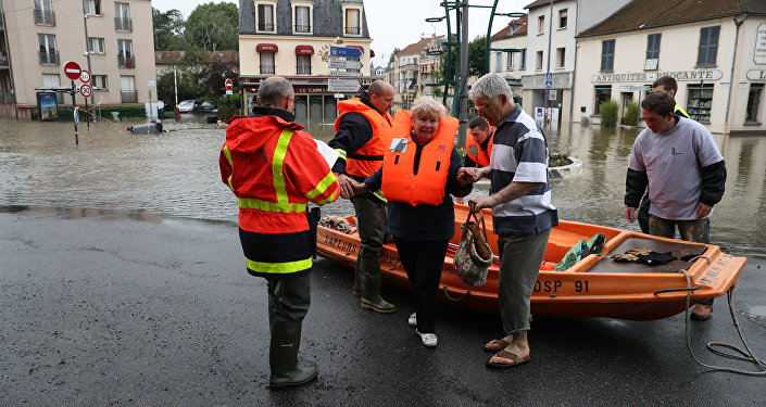 Firefighters evacuate people in a small boat from a flooded street after the Yvette river burst its banks and forced residents to be evacuated in Longjumeau, some 20kms south of Paris, on June 2, 2016