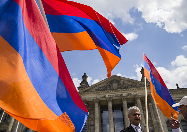 Armenian activists wave flags outside the Bundestag after law makers voted to recognise the Armenian genocide after a debate during the 173rd sitting of the German lower house of parliament, in Berlin on June 2, 2016