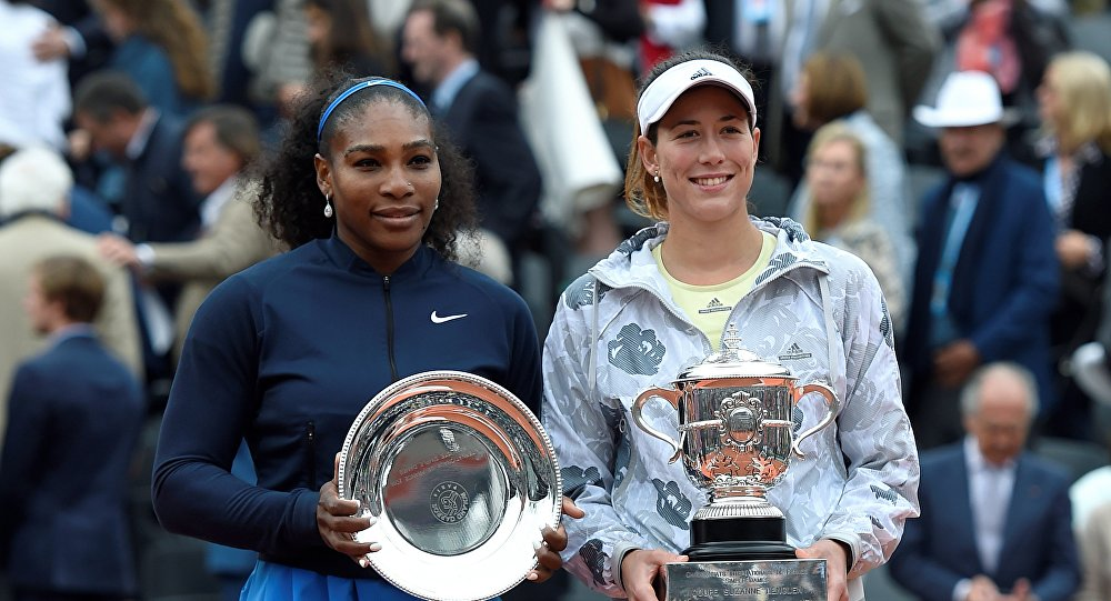US player Serena Williams (L) and winner Spain's Garbine Muguruza pose with their trophy after their women's final match at the Roland Garros 2016 French Tennis Open in Paris on June 4, 2016