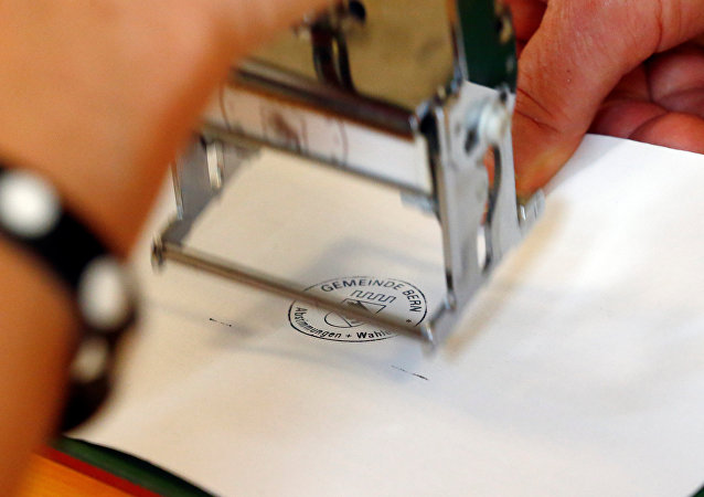 A ballot paper gets a stamp in a ballot office during a vote on whether to give every adult citizen a basic guaranteed monthly income of 2,500 Swiss francs ($2,560), in a school in Bern, Switzerland, June 5, 2016.