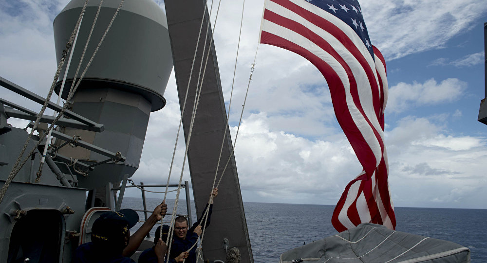 US Navy personnel raise their flag