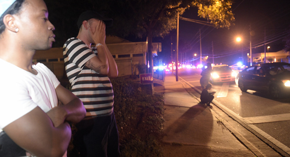 Jermaine Towns, left, and Brandon Shuford wait down the street from a multiple shooting at a nightclub in Orlando, Fla., Sunday, June 12, 2016