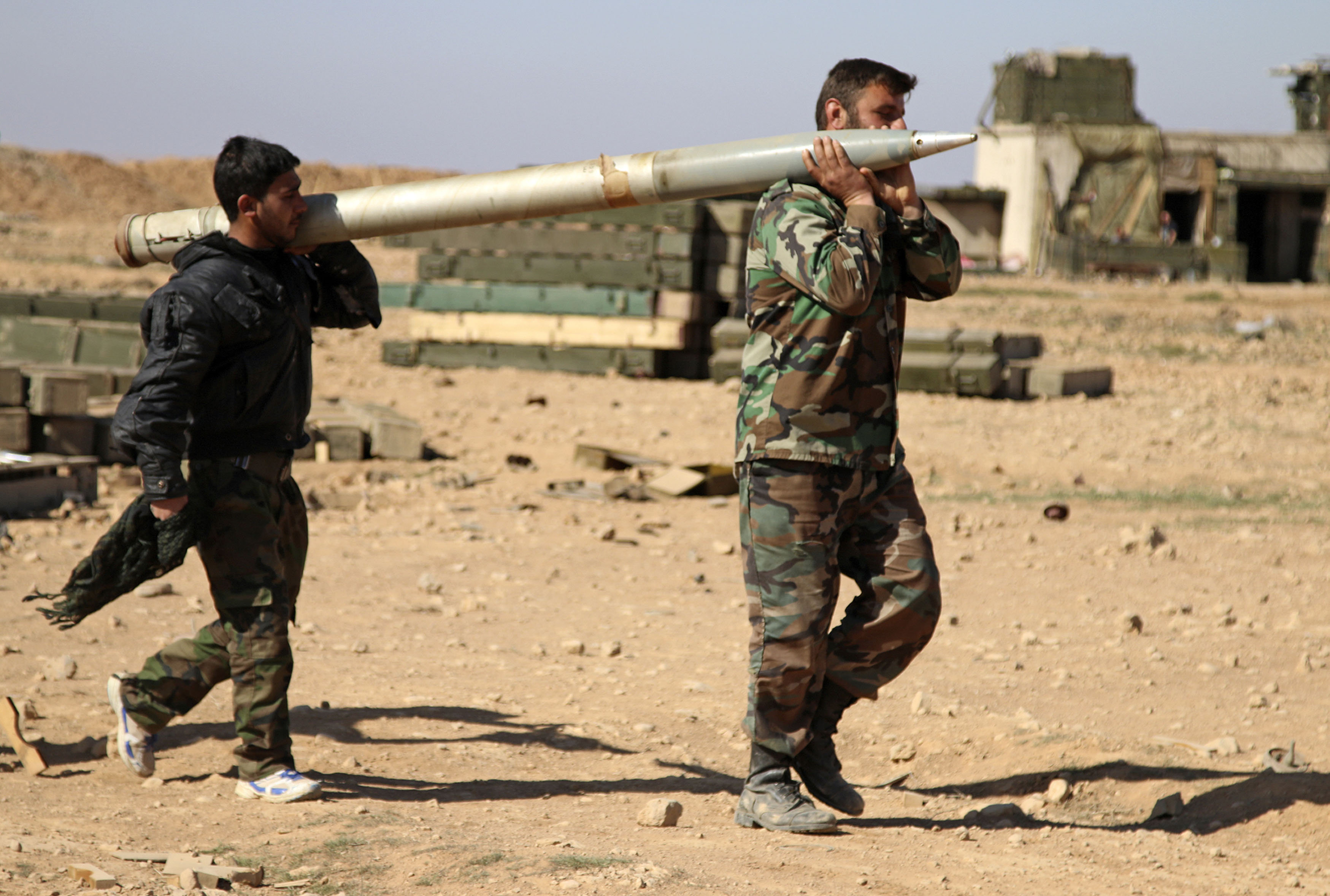 Soldiers from the Syrian army carry a rocket to fire at Daesh positions in the province of Raqqa, Syria