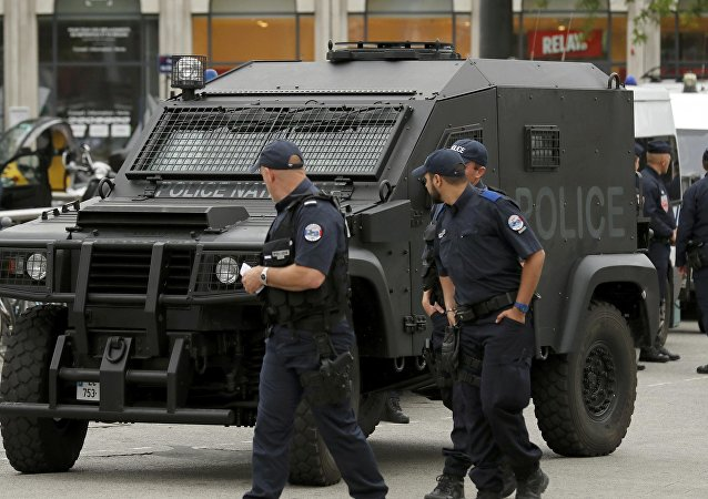 A police patrol looks at an armoured police vehicle parked in front of the train station in Lille, France.