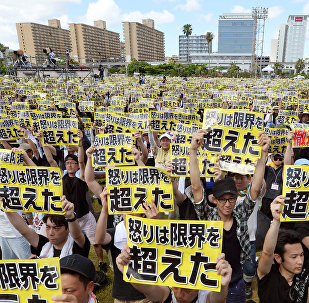 Protesters raise placards reading Anger was over the limit during a rally against the U.S. military presence on the island and a series of crimes and other incidents involving U.S. soldiers and base workers, at a park in the prefectural capital Naha on Japan's southern island of Okinawa, Japan, in this photo taken by Kyodo June 19, 2016