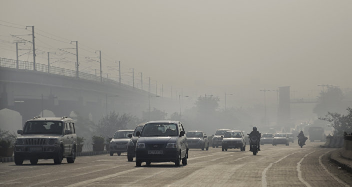 Vehicles move through morning smog on the first day of a two-week experiment to reduce the number of cars to fight pollution in New Delhi.