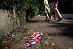 A British flag which was washed away by heavy rains the day before lies on the street in London, Britain, June 24, 2016 after Britain voted to leave the European Union in the EU BREXIT referendum.