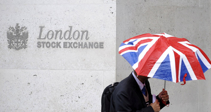 A worker shelters from the rain as he passes the London Stock Exchange in the City of London at lunchtime