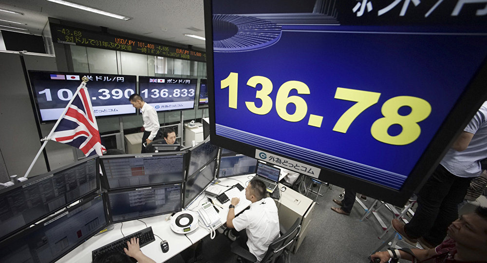 A computer screen shows the day's ongoing exchange rate between yen and the British pound, top, at a foreign exchange brokerage at a securities firm in Tokyo, Friday, June 24, 2016